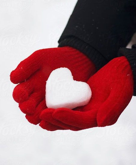 child in red gloves holding a snow heart